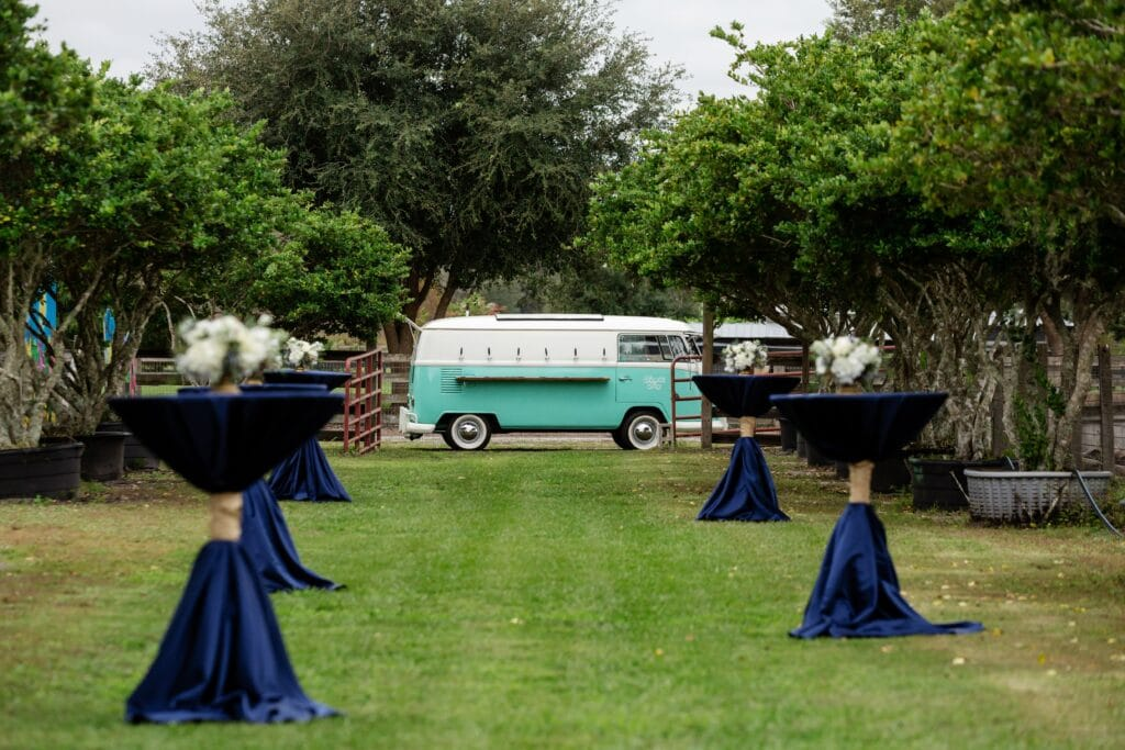 teal and white van mobile bar at outdoor wedding reception with navy cocktail tables